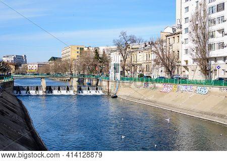 Bucharest, Romania, 13 February 2021 - Small Bridge, Old Buildings Near Dambovita River And Clear Bl
