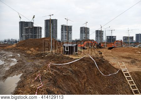 View Of A Large Construction Site. Excavator For Earthworks. Tower Cranes Are Building Multi-storey