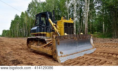 Dozer During Clearing Forest For Construction New Road . Yellow Bulldozer At Forestry Work Earth-mov