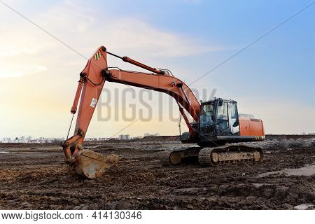 Excavator On Earthworks At Construction Site. Backhoe On Earthmoving And Foundation Work. Heavy Mach