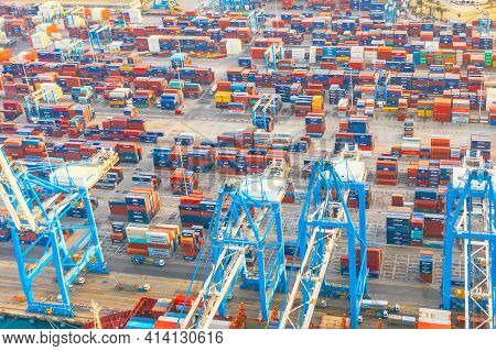 Aerial View From The Height Of A Cargo Harbor In A Cargo Seaport, A Sailing Ship With Containers Goo
