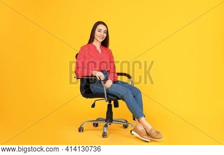 Young Woman Sitting In Comfortable Office Chair On Yellow Background