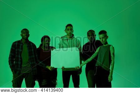 Peaceful Young Multiracial Protestors Holding Blank Placard While Standing Side By Side In Green Lig