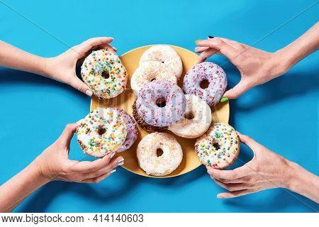 Dessert Table. Different Colourful Round Glazed Donuts With Sprinkles On Yellow Plate Over Blue Back
