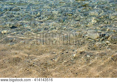Close-up Of Crystal Clear Sea Water With Stones Near Beach On Corfu Island In Greece. Background Wit