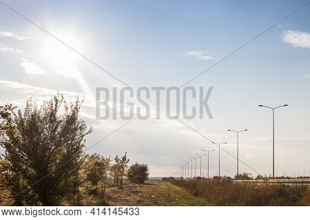 Rural Landscape With A Newly Built Freeway Motorway Road With Traffic Passing By Over During A Sunse