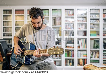 Man With Beard Playing Acoustic Blue Guitar Sitting In His Home Studio