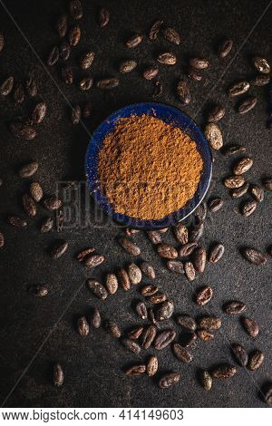 Cocoa powder and cocoa beans on black table. Top view.