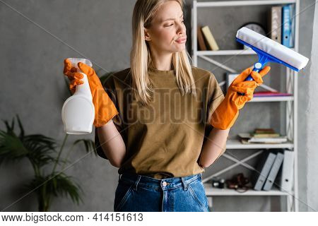 Displeasure european woman posing with streak and cleaning spray at home