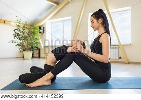 Little Girl Practices Yoga With A Private Trainer In The Studio. Young Beautiful Woman Trainer Helps