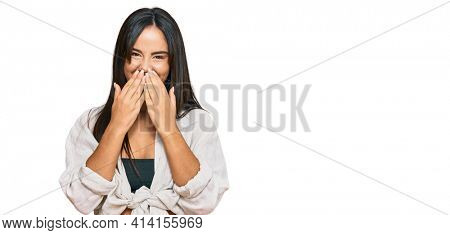 Young beautiful hispanic girl wearing casual clothes laughing and embarrassed giggle covering mouth with hands, gossip and scandal concept