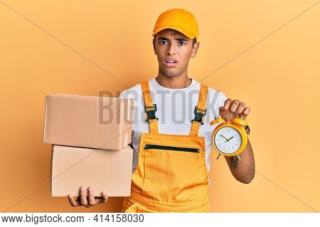 Young handsome african american man holding delivery box and alarm clock for express service clueless and confused expression. doubt concept.