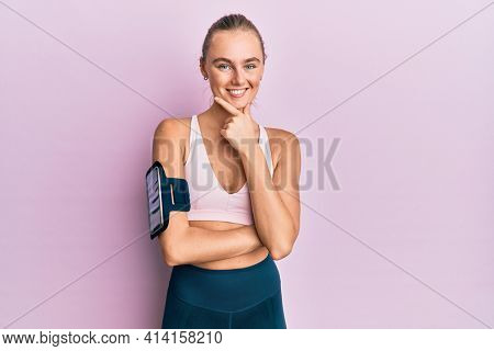 Beautiful blonde woman wearing sportswear and arm band looking confident at the camera with smile with crossed arms and hand raised on chin. thinking positive.