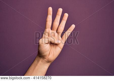 Hand of caucasian young man showing fingers over isolated purple background counting number 4 showing four fingers