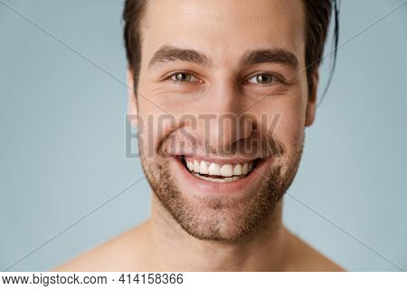 Close up of a smiling brunette shirtless man with stubble over blue background