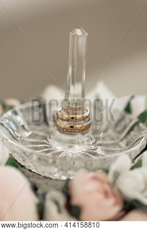 Wedding Day. Gold Wedding Rings On A Glass Saucer Decorated With Delicate Pink Flowers, A Solemn Cer
