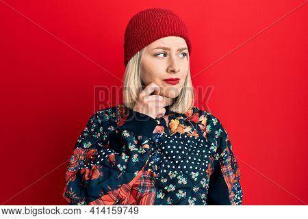 Young blonde woman wearing wool winter cap serious face thinking about question with hand on chin, thoughtful about confusing idea