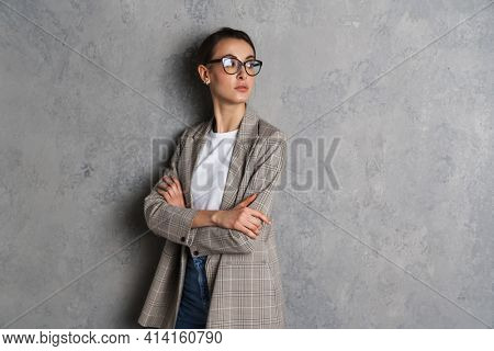 Confident attractive young casual woman wearing casual jacket standing isolated over background, arms folded, looking away