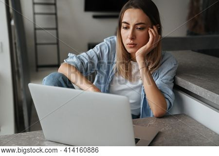 Upset disappointed young woman looking at laptop screen while sitting at home