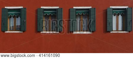 Four Windows Are Arranged In One Line On The Dark Red Wall. Open Green Shutters. Pattern And Free Sp