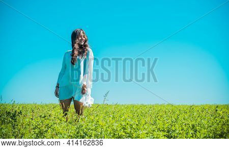 Freedom Concept. Young Happy Woman In Green Field, Evening Light. Blue Sky Behind. Beauty Girl Outdo
