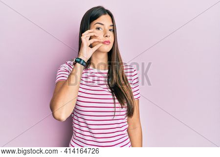 Young brunette woman wearing casual clothes over pink background mouth and lips shut as zip with fingers. secret and silent, taboo talking