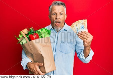 Middle age grey-haired man holding groceries and swiss franc banknotes afraid and shocked with surprise and amazed expression, fear and excited face.