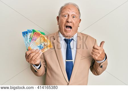 Senior caucasian man holding swiss franc banknotes pointing thumb up to the side smiling happy with open mouth
