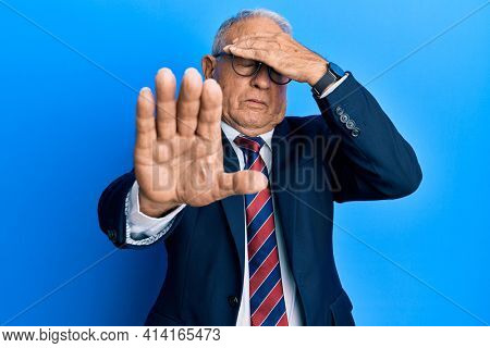 Senior caucasian man wearing business suit and tie covering eyes with hands and doing stop gesture with sad and fear expression. embarrassed and negative concept.