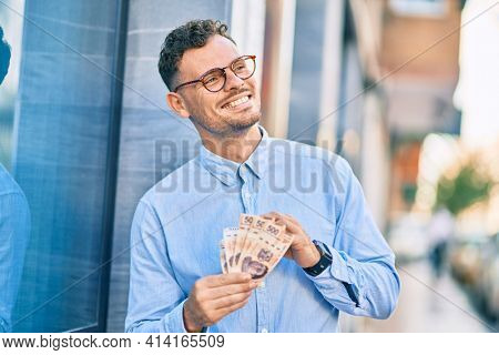 Young hispanic businessman smiling happy counting mexican 500 pesos banknotes at the city.