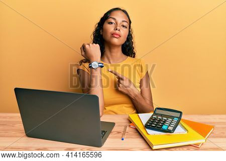 Young african american girl working at the office with laptop and calculator in hurry pointing to watch time, impatience, looking at the camera with relaxed expression