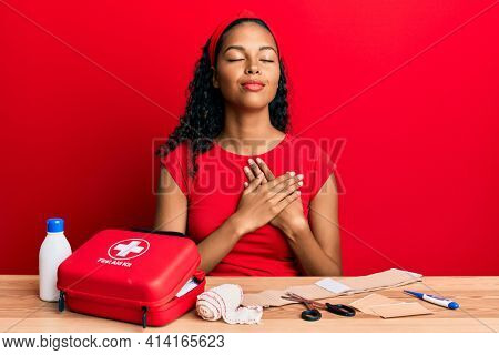 Young african american girl sitting on the table with first aid kit making cure smiling with hands on chest, eyes closed with grateful gesture on face. health concept.