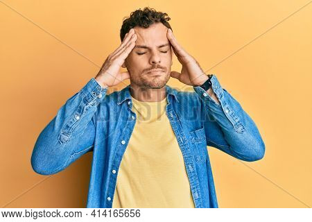 Young hispanic man wearing casual clothes with hand on head, headache because stress. suffering migraine.