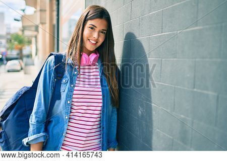 Young hispanic student girl smiling happy using headphones leaning on the wall at the city.