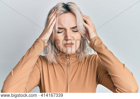 Young blonde girl wearing casual clothes with hand on head for pain in head because stress. suffering migraine.