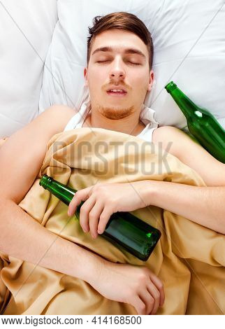 Drunk Young Man Sleep With A Beer Bottle In The Bed