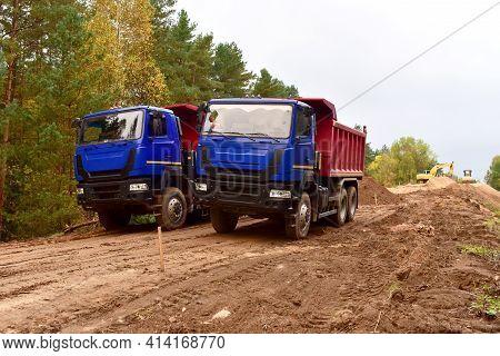 Dump Trucks Work On Road Construction In A Forest Zone. Tipper Truck Transport Sand For Roadworks Pr