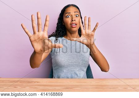 Young african american girl wearing casual clothes sitting on the table afraid and terrified with fear expression stop gesture with hands, shouting in shock. panic concept.