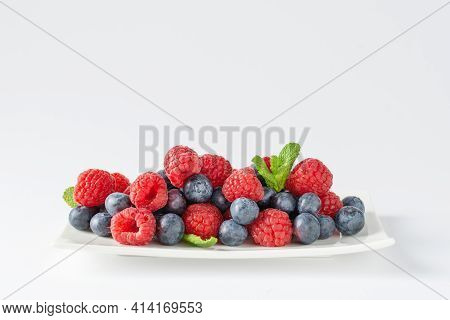 Fresh Blueberries And Raspberries Plate On White Background. Mix Of Wild Blueberry And Raspberry Ber
