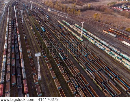 Drone shot over a railway sorting station with trains at sunset. Photo railway tracks with wagons, top view. Aerial top view.
