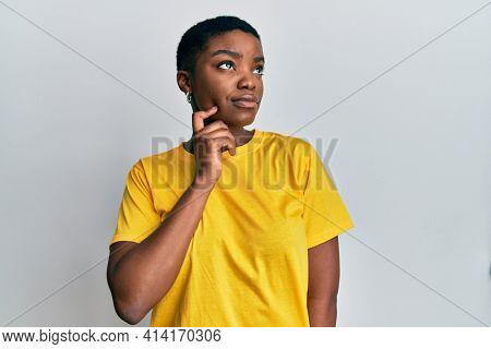 Young african american woman wearing casual yellow t shirt thinking concentrated about doubt with finger on chin and looking up wondering