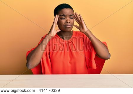 Young african american woman wearing casual clothes sitting on the table with hand on head, headache because stress. suffering migraine.