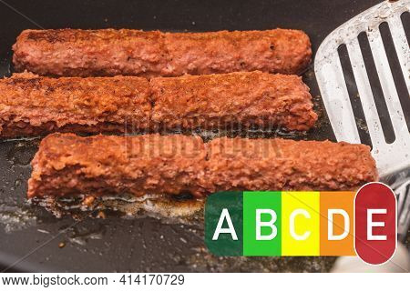 Nutri Score Food Labeling. Oily Frying Pan With Sausages - Cevapcici. Fatty Foods Have An E Red Nutr