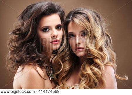 Portrait of stunning beauties with gorgeous wavy hair and jewerly. Blond and brunette.