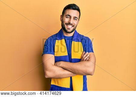 Young hispanic man football hooligan cheering game happy face smiling with crossed arms looking at the camera. positive person.