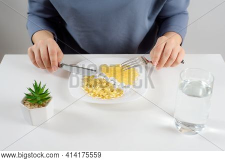 A Woman With A Knife And A Fork In Her Hands Is Going To Eat Vitamins Lying In Her Plate. Capsules O