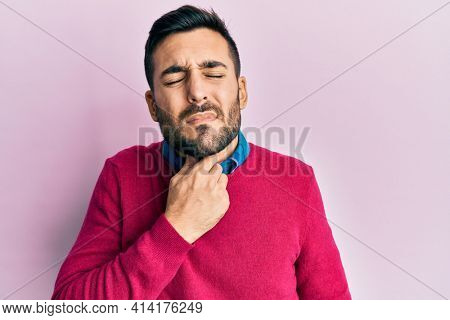 Young hispanic man wearing casual clothes touching painful neck, sore throat for flu, clod and infection