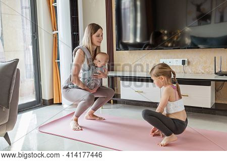Young Mother In Sport Clothing Exercising At Home With Baby. Online Training During Coronavirus Covi