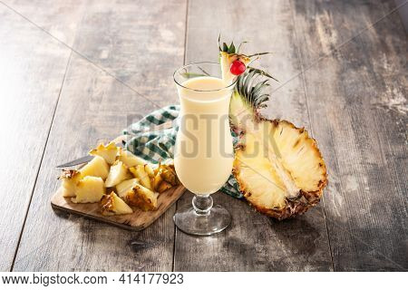 Pina Colada Cocktail In Glass On Wooden Table