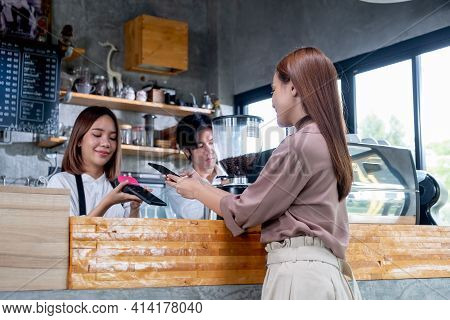 Asian Beautiful Woman Use Mobile Phone To Pay With Contactless Payment And Service By Barista Girl O